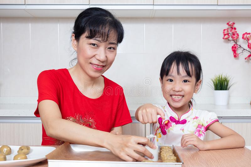Asian Chinese mother and daughter making moon cake in the kitchen stock photo