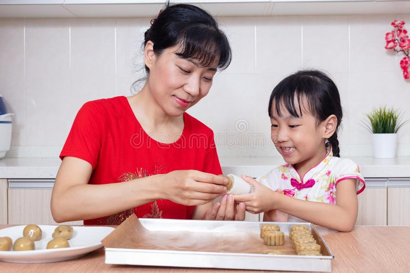 Asian Chinese mother and daughter making moon cake in the kitchen stock image
