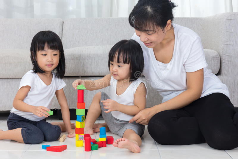 Asian Chinese mother and daughter playing blocks on the floor royalty free stock images
