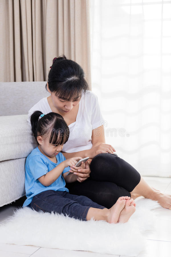 Asian Chinese mother and daughter using smartphone on the floor stock photography
