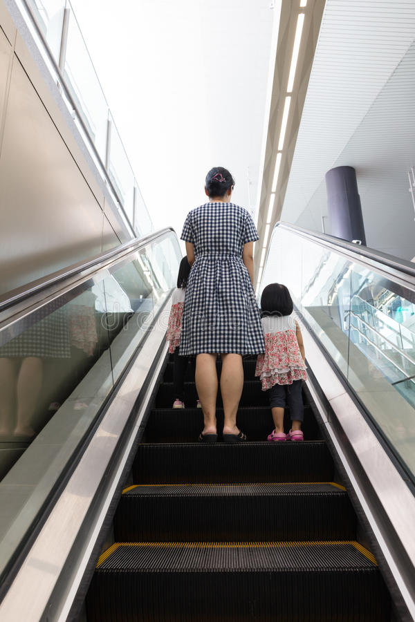 Asian Chinese mother and daughters taking escalator at MRT Station. In Kuala Lumpur, Malaysia royalty free stock photos
