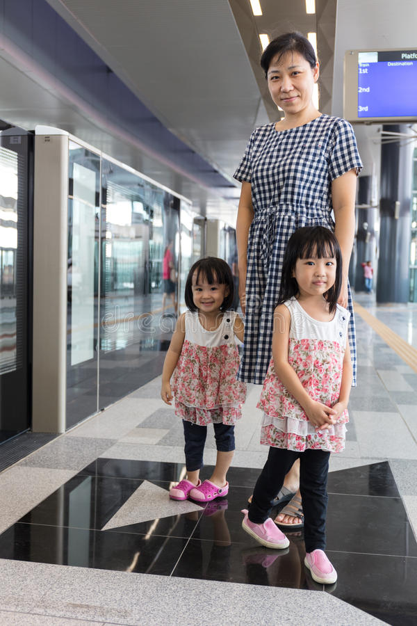 Asian Chinese mother and daughters waiting for transit at station. Asian Chinese mother and daughters waiting for transit at MRT station in Kuala Lumpur stock photos