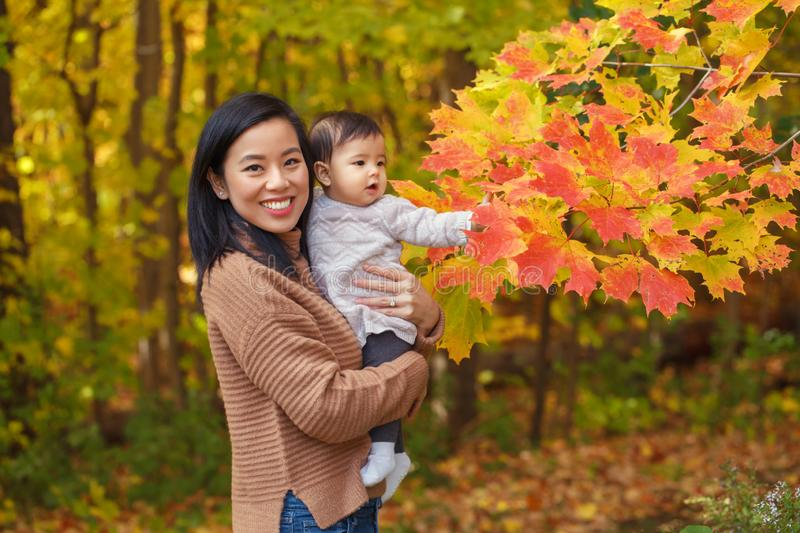 Asian Chinese mother holding cute adorable  baby girl on hands in autumn fall park outdoor royalty free stock images