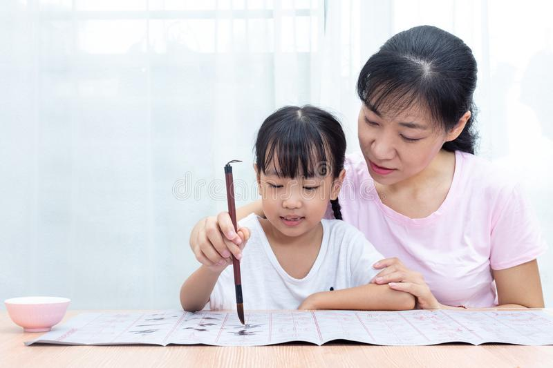 Asian Chinese mother teaching daughter practice Chinese calligraphy royalty free stock photos