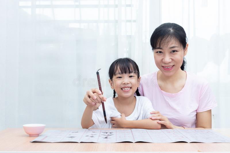 Asian Chinese mother teaching daughter practice Chinese calligraphy stock photography