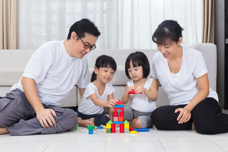 Asian Chinese parents and daughters playing blocks on the floor stock photography