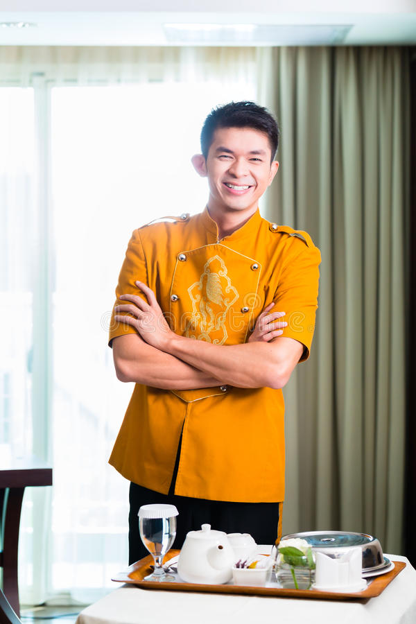 Asian Chinese room service waiter serving food in hotel suite royalty free stock image