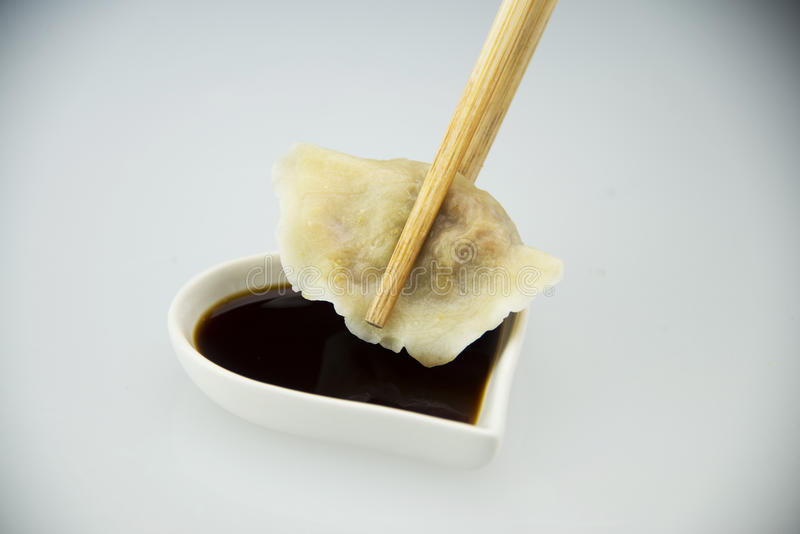 Asian Chinese traditional pasta Boiled dumplings,. Dumplings with chopsticks, with a little dish of vinegar, taste more delicious royalty free stock photos