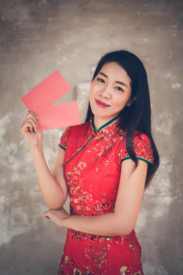 Asian Chinese Woman in Cheongsam Red Dress Holding Red Envelope for Giving Ang Pao in Chinese New Year royalty free stock images