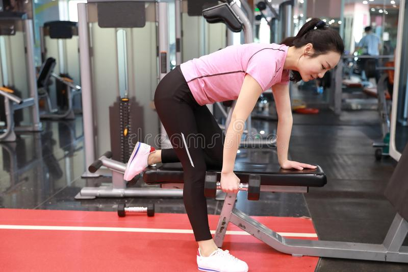 Asian chinese woman in gym ,Fitness young girl in the gym doing exercises with dumbbells stock photos