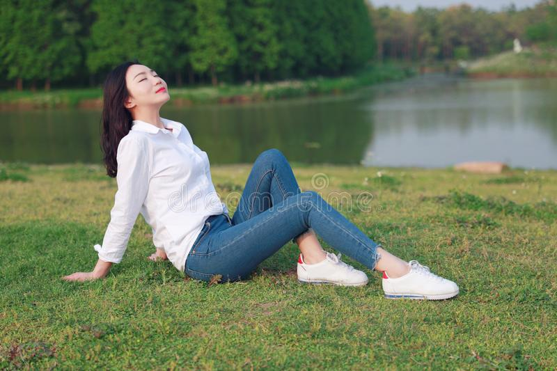 Aisan Chinese woman beautiful girl enjoy free causual time by a lake royalty free stock photos
