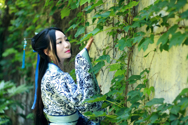 Asian Chinese woman in traditional Blue and white Hanfu dress, play in a famous garden near wall stock photo
