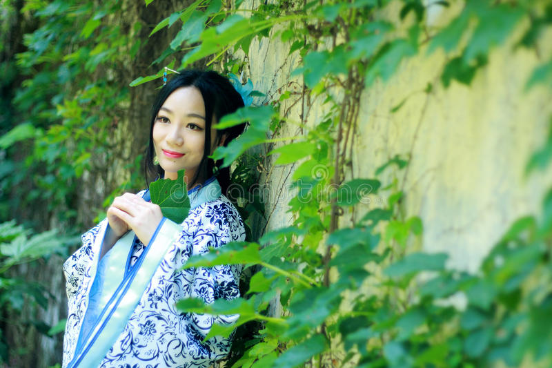 Asian Chinese woman in traditional Blue and white Hanfu dress, play in a famous garden near wall royalty free stock photos