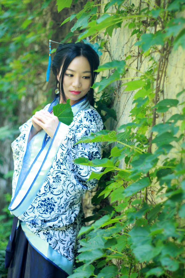 Asian Chinese woman in traditional Blue and white Hanfu dress, play in a famous garden near wall stock image