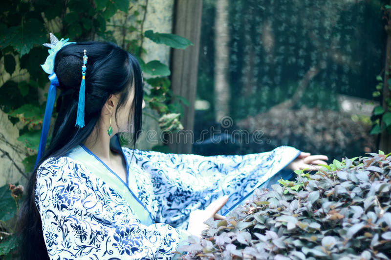 Asian Chinese woman in traditional Blue and white Hanfu dress, play in a famous garden near wall stock photography