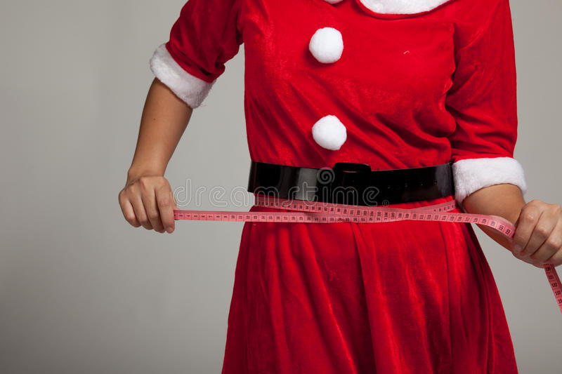 Asian Christmas girl in Santa Claus clothes diet with measuring royalty free stock photography