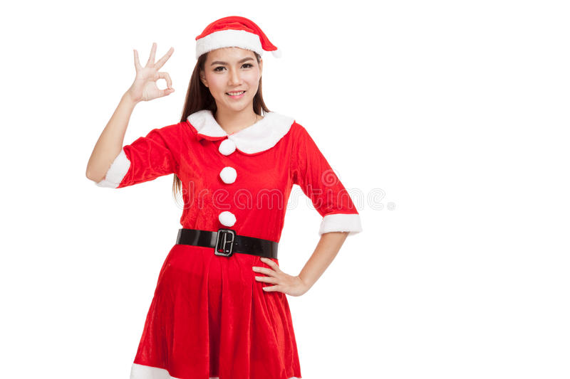 Asian Christmas girl with Santa Claus clothes show Ok sign royalty free stock images