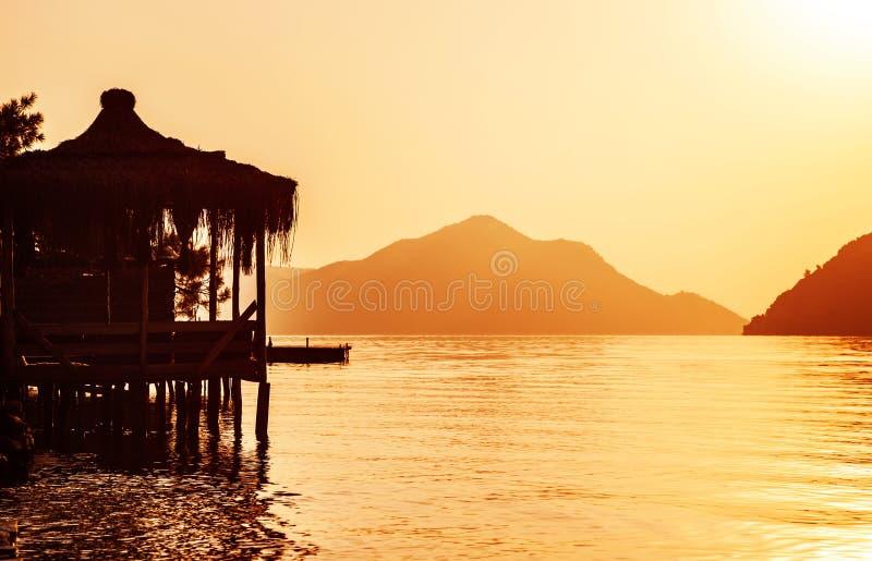 Asian coastal resort. Image of Asian coastal luxury resort, beautiful little hut on the water, orange sunset, paradise beach, cute bungalow on sea shore stock photo