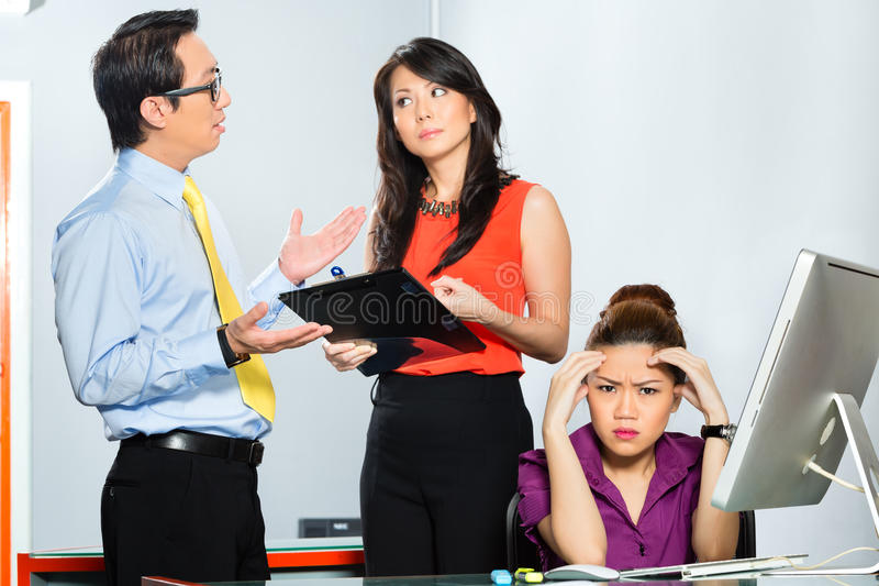 Asian colleagues mobbing or bullying employee royalty free stock photos