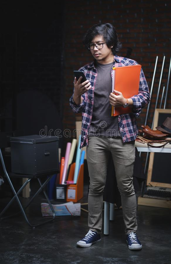 Asian College Student Checking Phone and Holding Books Inside Wa royalty free stock photos