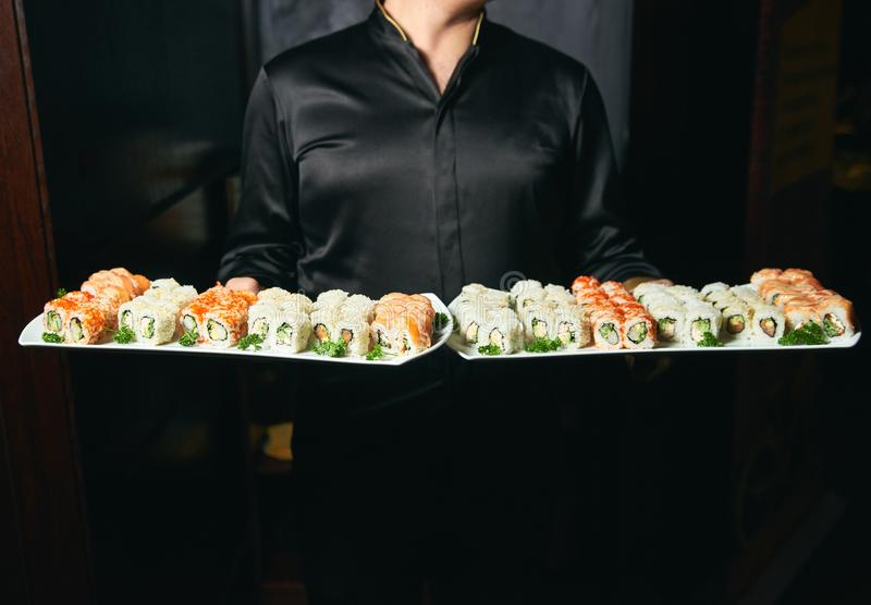Asian cook hold a sushi roll dish. Professional chef or waiter with sushi food dish on plates in restaurand cafe stock images