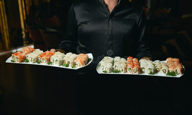 Asian cook hold a sushi roll dish. Professional chef or waiter with sushi food dish on plates in restaurand cafe stock photography