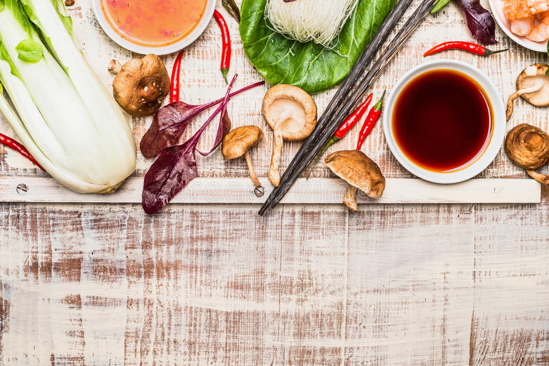 Asian cooking ingredients with chopsticks on rustic wooden background, top view stock photo
