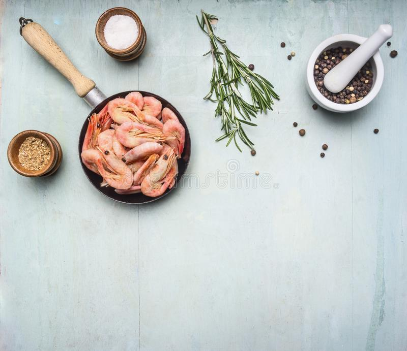 Asian cooking ingredients with fresh small shrimp in a small frying pan, herbs and pepper wood blue background top view border,. Asian cooking ingredients with royalty free stock images