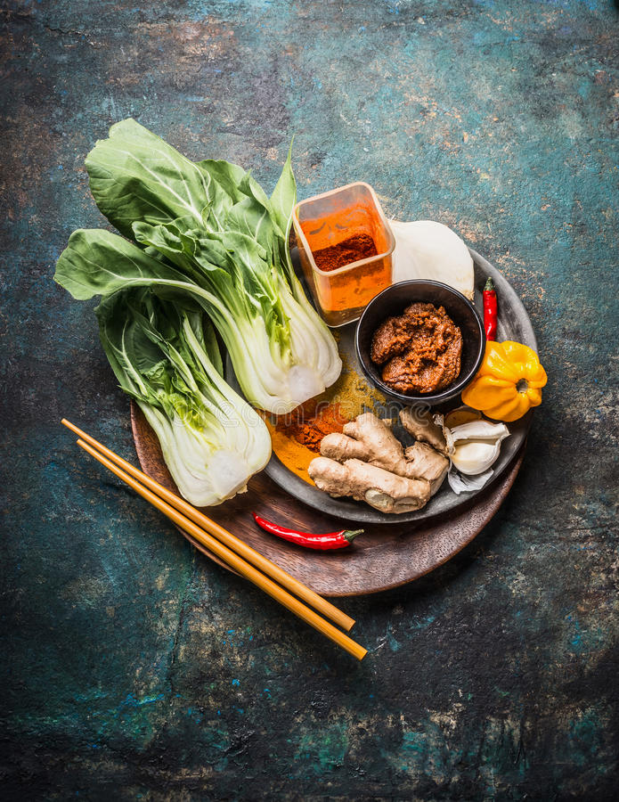 Asian cooking ingredients with pak choi , ginger, spices, chili and chopsticks on wooden dish for Chinese or Thai cuisine on dark royalty free stock photos