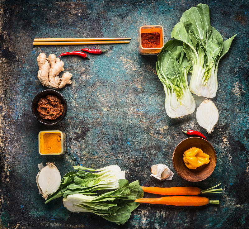 Asian cooking ingredients and spices with chopsticks on rustic background , top view , place for text, frame. Asian food and eatin royalty free stock images