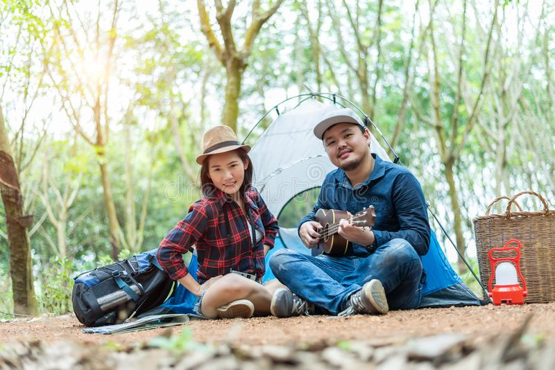 Asian couple camping in the forest. Man playing ukulele with woman in front of camping tent. Lamp and basket and backpack element stock images