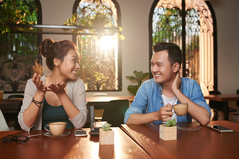 Asian Couple Chatting in Cafe stock photos