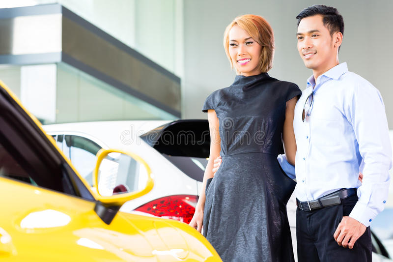 Asian couple choosing roadster car in dealership. Asian couple choosing luxury sports car in auto dealership looking at a roadster stock image