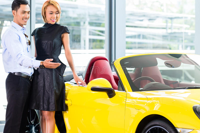 Asian couple choosing roadster car in dealership. Asian couple choosing luxury sports car in auto dealership looking at a roadster royalty free stock images
