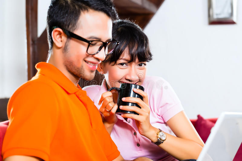 Asian couple on the couch with a laptop. Indonesian couple sitting home on sofa with laptop using the internet for email and online shopping stock photo