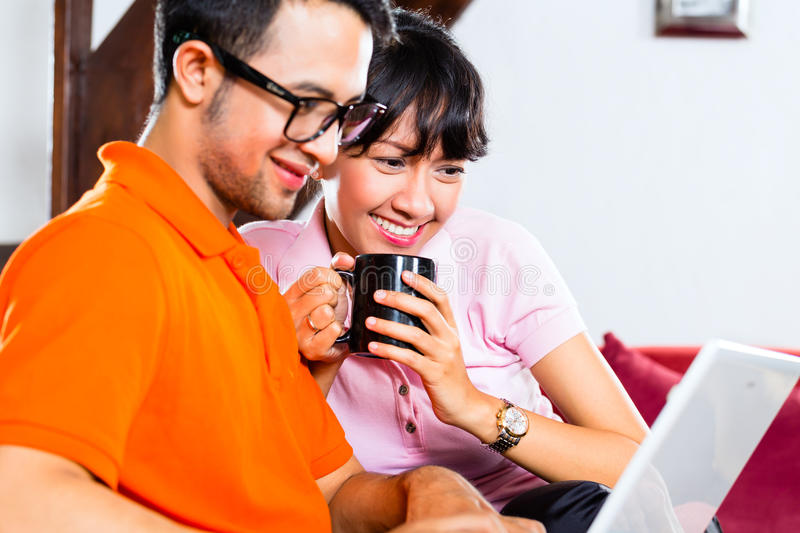 Asian couple on the couch with a laptop. Indonesian couple sitting home on sofa with laptop using the internet for email and online shopping stock photos