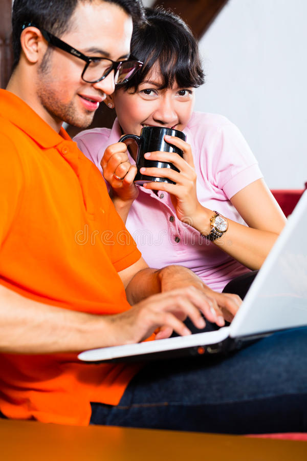Asian couple on the couch with a laptop. Indonesian couple sitting home on sofa with laptop using the internet for email and online shopping royalty free stock photo