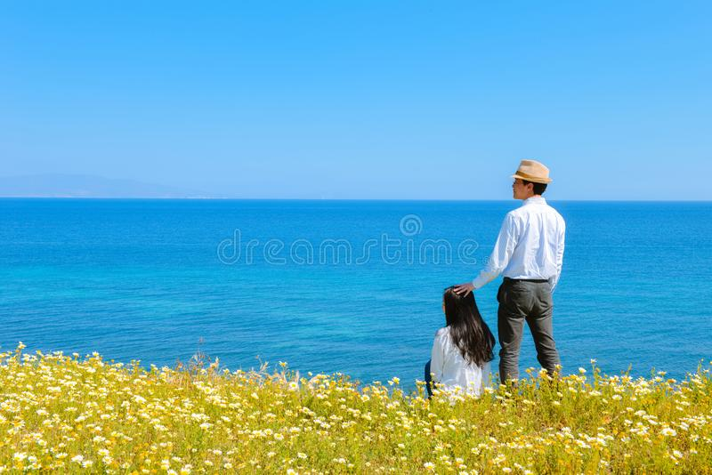 Asian couple together among flowers on Santorini island. Asian couple enjoy Spring time among blossoms by Aegeon sea on on Santorini island, Greece royalty free stock photography