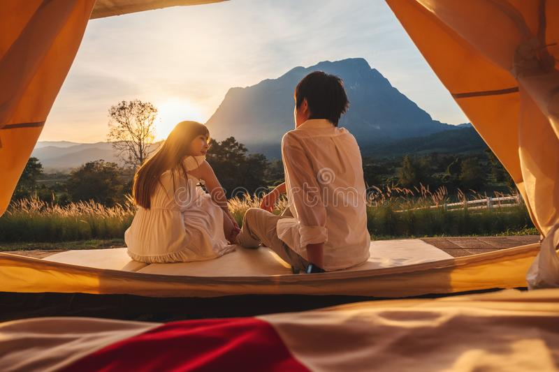 Asian couple enjoying outdoor camping Watching the sunset in nature stock images