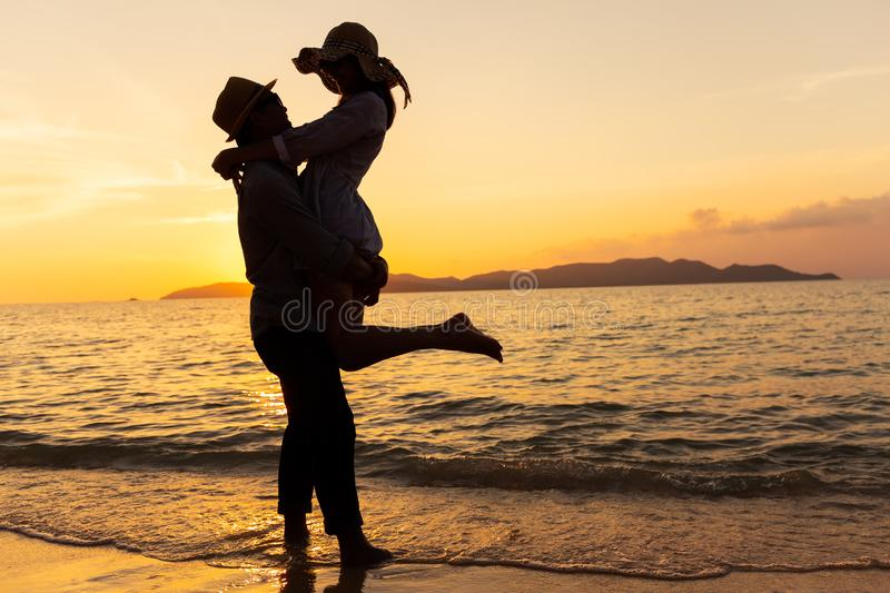 Asian couple expressing their feeling while standing at beach, Young couples hug at the sea at sunset royalty free stock images