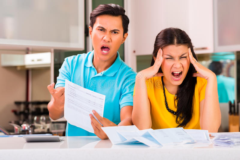Asian couple fighting unpaid bills royalty free stock image