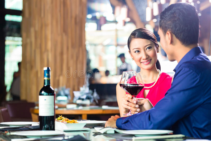 Asian couple fine dining in restaurant. Asian couple having dinner and drinking red wine in very fancy restaurant with open kitchen in background stock image