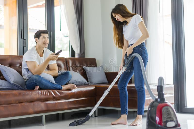 Asian couple girl doing floor cleaning with vaccuum cleaner while man on a brown sofa at home. stock image