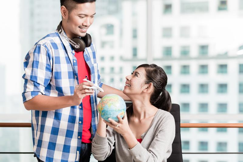 Asian couple with globe and model airplane in urban apartment royalty free stock photos