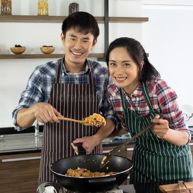 Asian couple are happy to cook together in the morning. Young Asian couple are happy to cook together, two families are helping each other prepare to cook in the royalty free stock photos