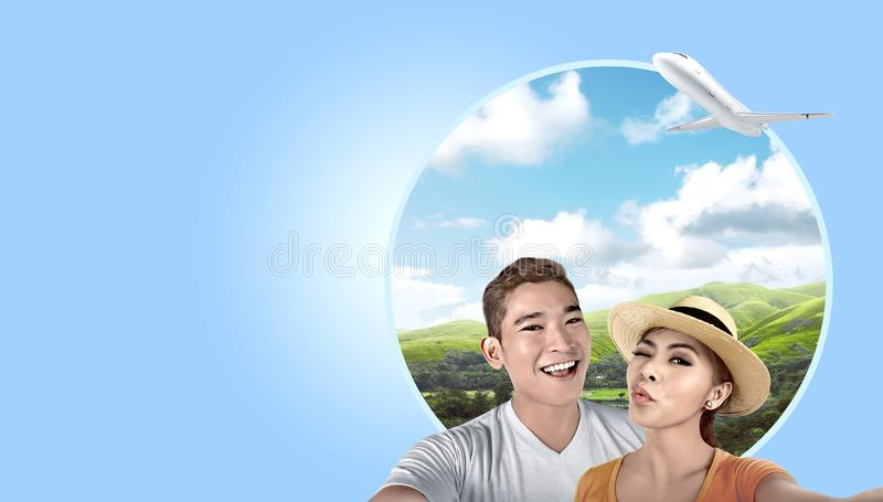 Asian couple with hat taking a selfie with green hills background stock photo