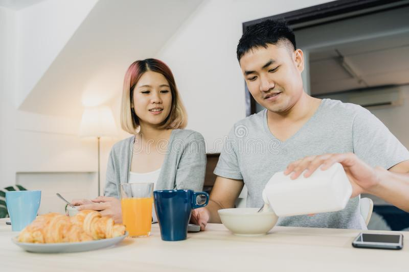 Asian couple having breakfast, cereal in milk, bread and drinking orange juice after wake up in the morning. royalty free stock photos