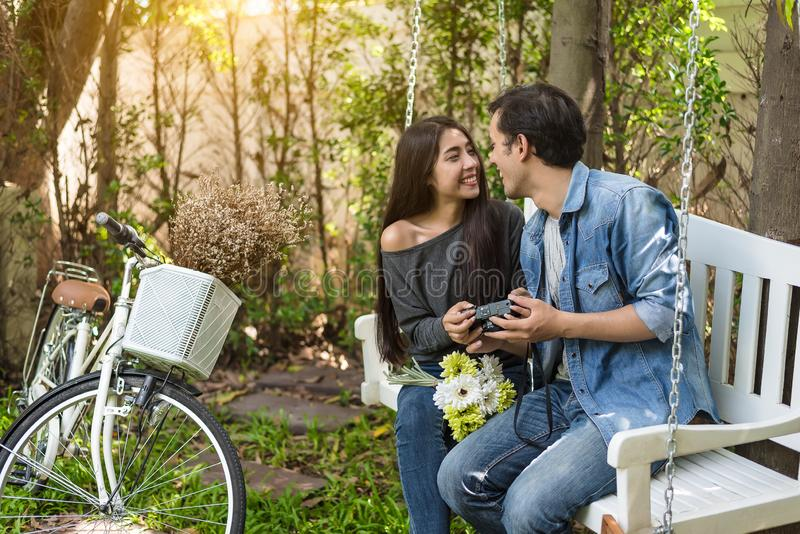 Asian couple having eye contact as romantic moment at bench in n. Atural park with bicycle. People and lifestyles concept for Valentines day and wedding ceremony stock photography
