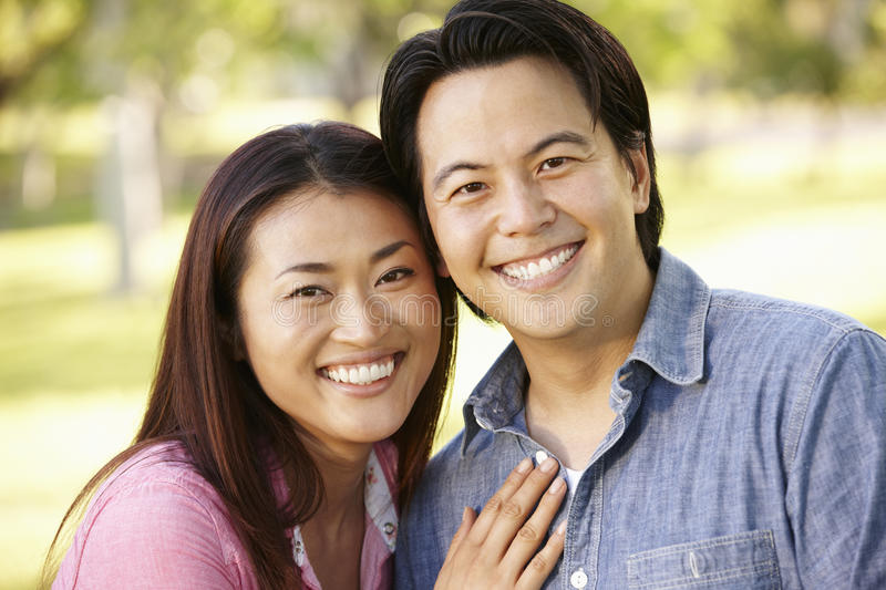 Asian couple head and shoulders portrait outdoors stock image
