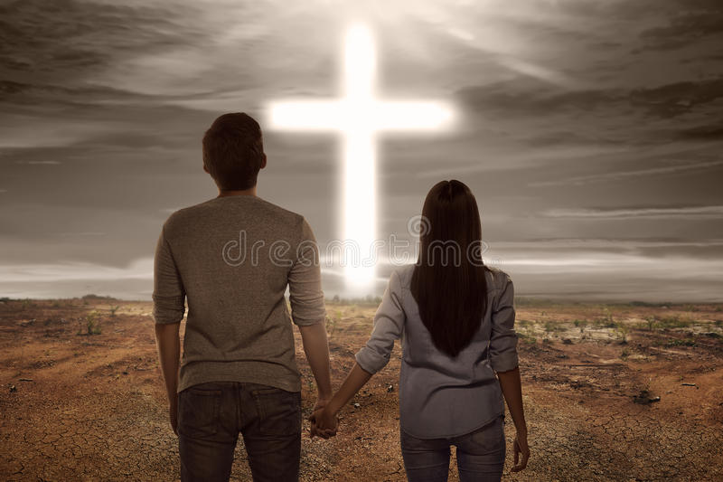 Asian couple holding hand each other looking bright cross shape stock photos